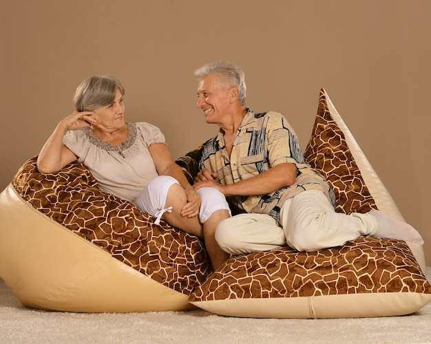 Cute old couple sitting at at armchairs on brown background