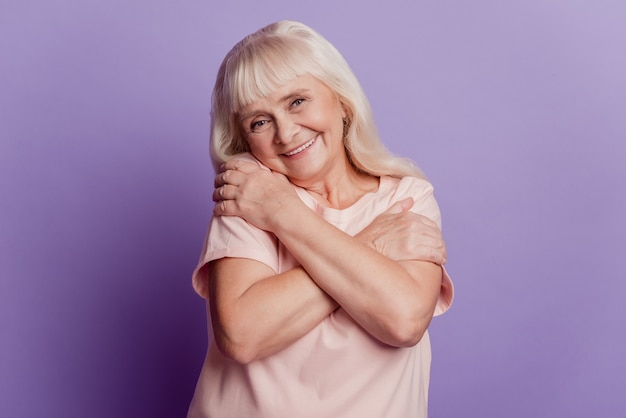 Cute old lady embracing herself isolated on purple background