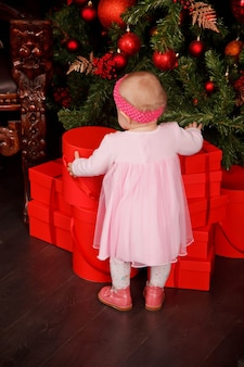 크리스마스 트리 장식 장난감을 배경으로 분홍색 드레스를 입은 귀여운 한 살짜리 소녀. 선물 상자 장식에 아이입니다. 아늑한 집 해피 뉴 이어 축하의 개념입니다. 복사 공간