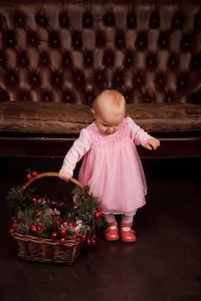 핑크색 드레스를 입은 귀여운 한 살짜리 소녀가 바구니와 함께 소파 배경에 크리스마스 장식된 장난감을 가지고 있습니다. 선물 선물 장식에 아이입니다. 아늑한 집 해피 뉴 이어 축하의 개념입니다. 복사 공간