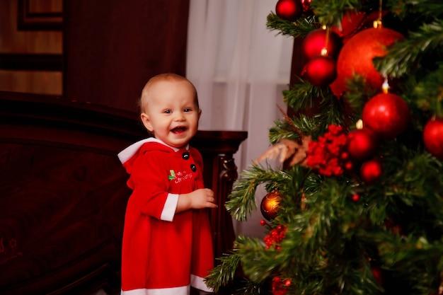 장난감으로 장식된 크리스마스 트리 배경에 산타클로스 의상을 입은 귀여운 한 살짜리 소녀. 선물 상자 장식에 아이입니다. 아늑한 집 해피 뉴 이어 축하의 개념입니다. 복사 공간
