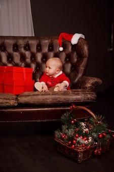 크리스마스 장난감과 물건으로 장식된 소파에 산타클로스 의상을 입은 귀여운 한 살짜리 소녀. 선물 상자 장식에 아이입니다. 아늑한 집 해피 뉴 이어 축하의 개념입니다. 복사 공간