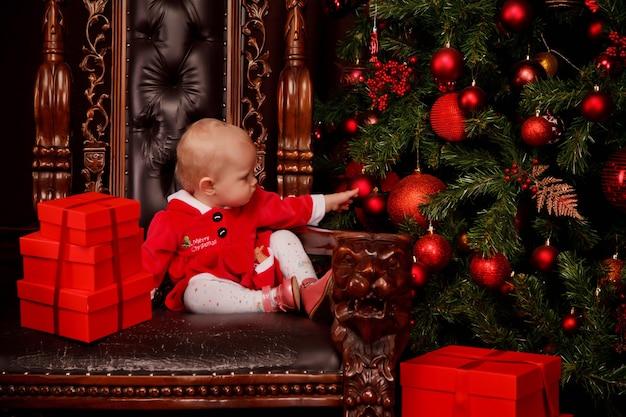 크리스마스 트리 장식 장난감의 배경에 왕좌에 산타 클로스 드레스에 귀여운 한 살짜리 소녀. 선물 상자 장식에 아이입니다. 아늑한 집 해피 뉴 이어 축하의 개념입니다. 복사 공간