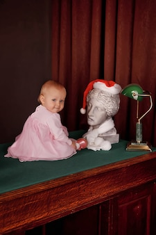 Cute one-year-old girl in pink dress in an old office sitting on desktop. child in interior of home office on table. concept of education and business children. background for website. copy space