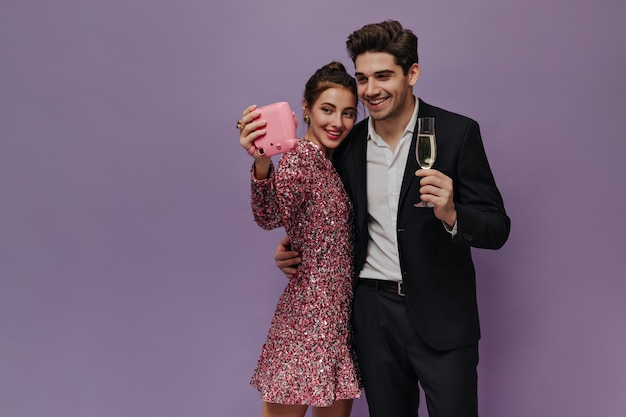 Cute pair of young people standing in party outfits, smiling and making selfie against light purple wall