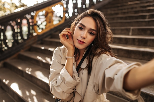 밝은 화장과 검은 머리를 한 귀여운 창백한 소녀가 베이지색 트렌치 코트를 입고 셀카를 찍고 야외에서 아름다운 포즈를 취합니다.