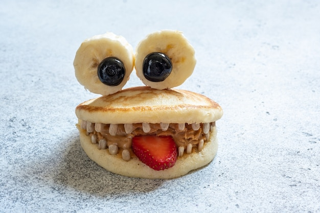Cute pancake monster with banana eyes and sunflower seeds tooth