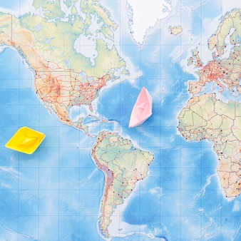Cute paper boats on map