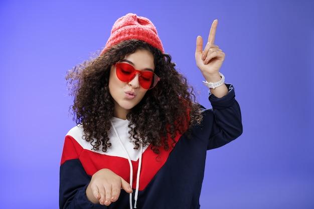 귀여운 파티 소녀는 세련된 빨간 선글라스와 따뜻한 모자를 쓰고 푸른 벽 너머로 파티에서 음악을 감상하며 신나게 춤추는 멋진 노래를 즐기면서 입술을 접는 디스코 동작을 하는 것을 즐기고 있습니다.
