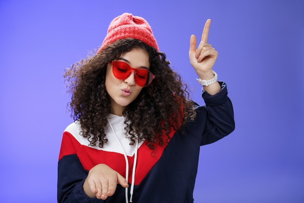 Cute party girl having fun making disco movements folding lips as enjoying cool song dancing joyfully wearing stylish red sunglasses and warm hat looking down enjoying music at party over blue wall.