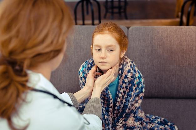 귀여운 환자. 그녀의 목을 확인하는 동안 소파에 앉아 좋은 빨간 머리 소녀