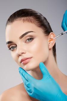Cute patient with nude make up at studio background, doctor's hands wearing blue gloves near patient's face, holding syringe with botex near face, beauty concept.