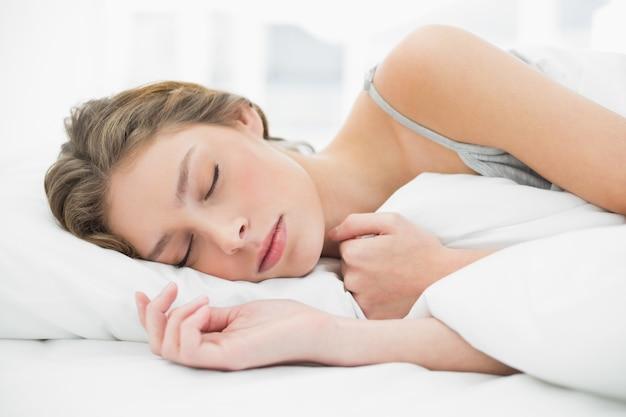 Симпатичная мирная женщина, дремлет, лежащая под покровом на кровати