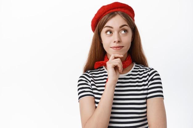 かわいい物思いにふける女の子は微笑んで、興味を持って脇を見て、何かを考えて、白い壁に立っています