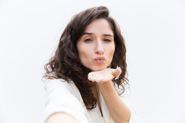 Cute pensive student girl sending air kiss