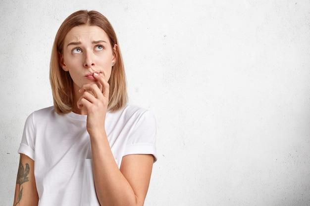 かわいい物思いにふける若い女性は、考えを持って集まり、考えながら上向きに見え、疑いを抱き、腕に入れ墨をし、カジュアルな白いtシャツを着て、スタジオの壁に隔離されています