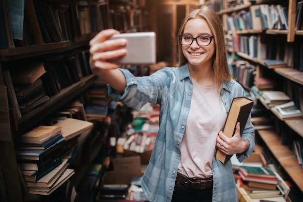 A cute picture of a blonde girl taking selfie. she is looking to the phone and smiling. this girls is in a big public library.
