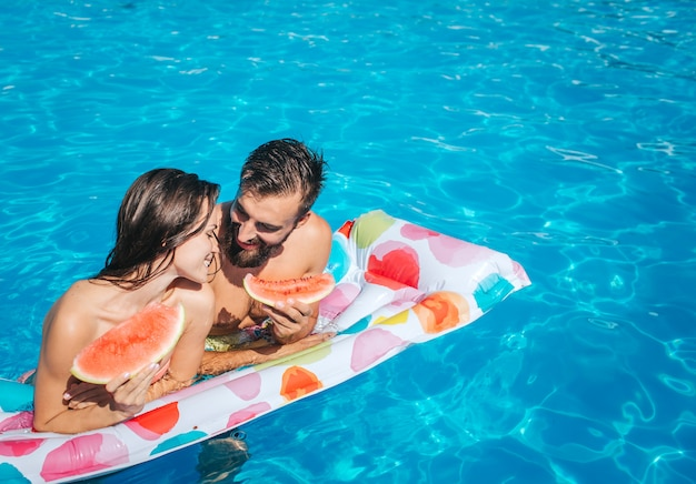 Cute picutre of young man and woman leaning to air mattress and hold pieces of watermelon. they look at eac other and smile. couple is in swimming pool.