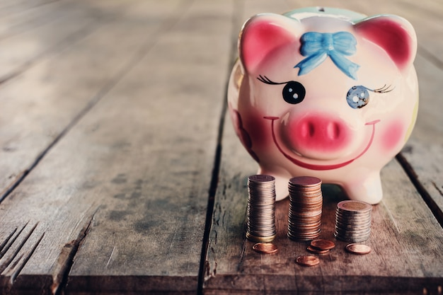 Cute piggy bank with coin on old wooden table
