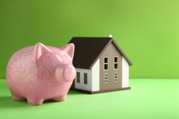 색상 배경에 집 모델이 있는 귀여운 돼지 저금통