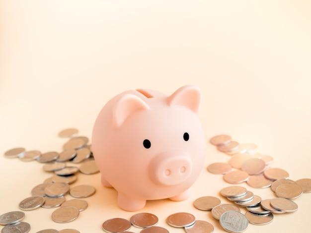 柔らかいベージュの表面にタイバーツのコインの山を持つかわいい貯金箱