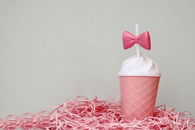 Симпатичная розовая пластиковая чашка для напитков с розовым бантом на белой коктейльной соломке.