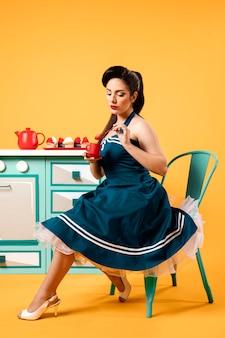 Ragazza carina pinup in cucina