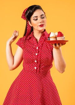 Cute pinup girl posing with cupcakes