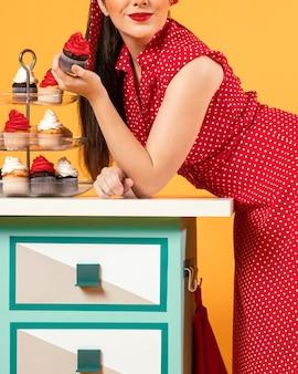 いくつかのカップケーキの隣に立っているかわいいピンナップガール
