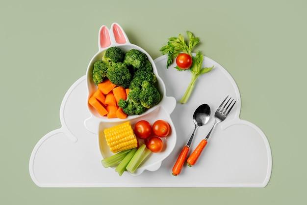新鮮な野菜とうさぎの形をしたかわいいプレート。子供のための食品のアイデア。にんじんとブロッコリーを使った子供の健康食品