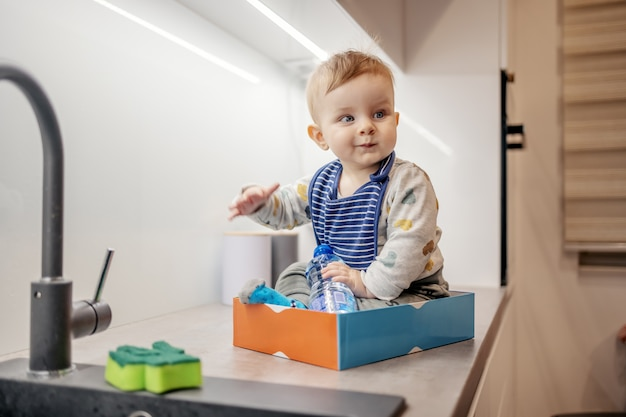 Cute playful caucasian blond little boy sitting in box on kitchen counter and playing as if he is in a train.