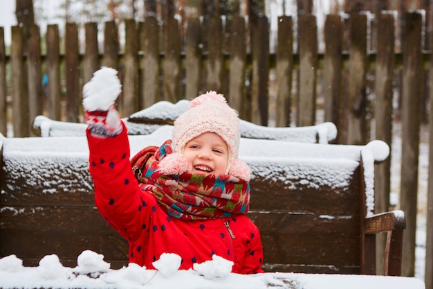 最初の雪を楽しんで屋外でかわいい遊び心のある女の子。