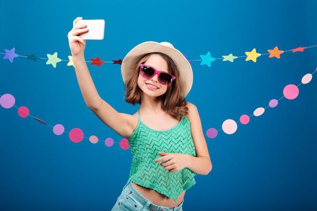 Милая игривая маленькая девочка в шляпе и солнцезащитных очках, делающая селфи с мобильным телефоном на синем фоне