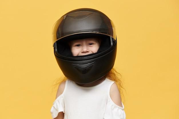 彼女の父から取られた黒いオートバイのヘルメットをかぶっているかわいい遊び心のある少女。笑顔で、保護モーター機器で隔離ポーズをとって面白い女児