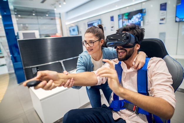 Cute playful love couple having fun with vr goggles in the tech store.