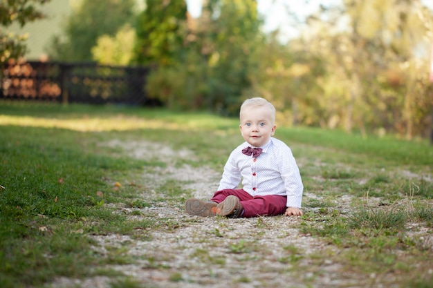 Cute playful smiled blond. 1 years old boy sitting on green grass outdor.