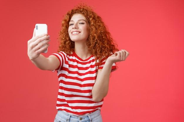 Милая довольная счастливая симпатичная рыжая рыжая девушка с кудрявой прической улыбается идеальной зубастой усмешкой ...