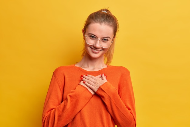 Cute pleased satisfied girl presses hands to heart, appreciates nice gift, looks gratefully being full of love and kindness smiles tenderly wears optical glasses, orange jumper stands indoor