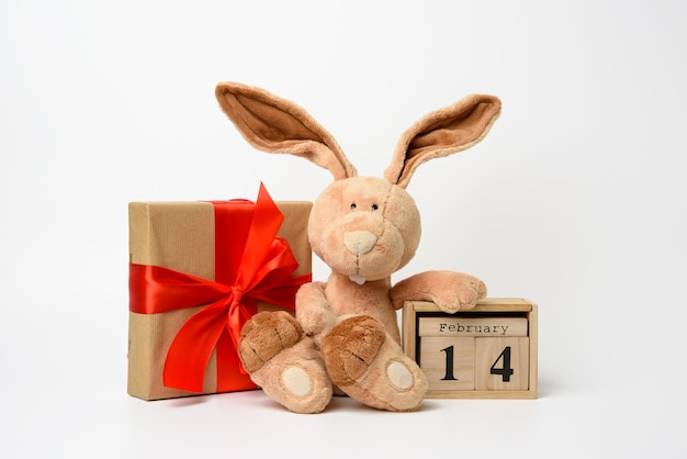 Cute plush rabbit and a box with a gift tied with a red silk ribbon, white background. wooden calendar with date 14 february