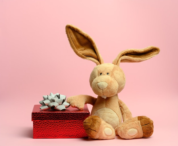 Cute plush rabbit holding a red gift box, pink wall