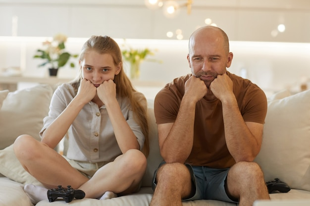 Cute portrait of mature father and teenage girl posing together while playing video games sitting on couch in cozy home interior