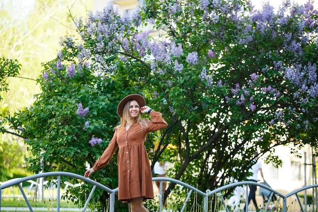 植物園のライラックの背景に茶色の帽子をかぶった女の子のかわいい肖像画。長いブロンドの髪が肩にあります