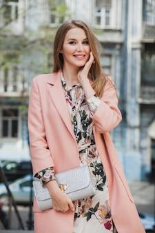 Симпатичный портрет привлекательной стильной улыбающейся женщины, идущей по городской улице в розовом пальто, весенняя мода, держащая сумочку