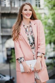 ピンクのコートで街を歩いて魅力的なスタイリッシュな笑顔の女性のかわいい肖像画