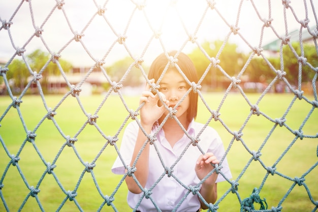 太陽の光でロープネット探しカメラの後ろに立つ無邪気なアジアの女の子の十代の学生のかわいい肖像画