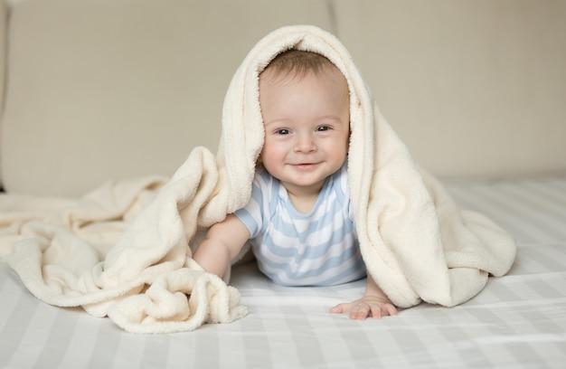 Милый портрет улыбающегося мальчика, лежащего на кровати под белым одеялом