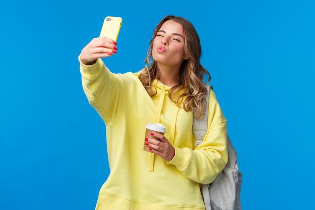 Симпатичная позитивная и женственная красивая молодая студентка, возглавляющая колледж, держит бумажный стаканчик из любимого кафе и рюкзак с книгами, принимая селфи шоу поцелуй mwah face на мобильный