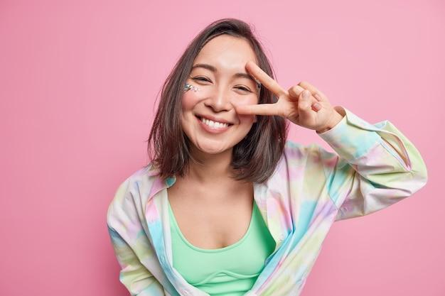 Симпатичная позитивная азиатская женщина с темными волосами показывает знак мира жестом v, выглядит счастливо одетым в повседневную рубашку, наслаждается хорошим днем, изолированным над розовой стеной, выражает беззаботные эмоции.