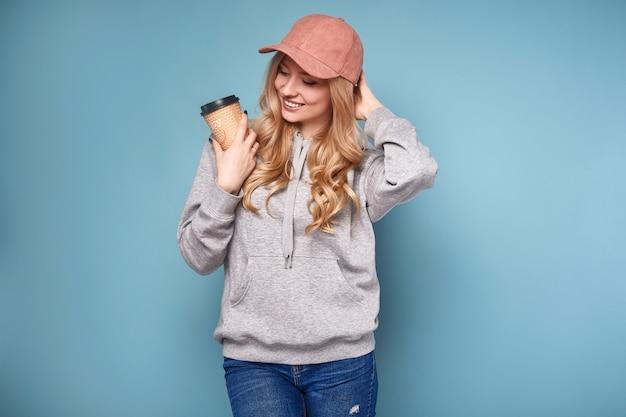 Милая позитивная блондинка в розовой кепке с кофе