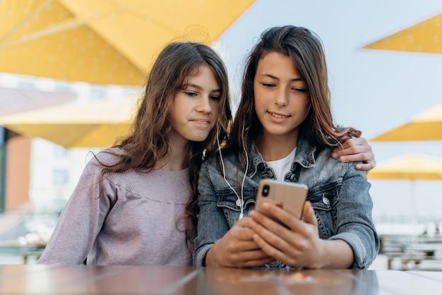 귀엽고 긍정적인 소녀들이 야외 테이블에 앉아 전화를 보고 있습니다. 스마트폰을 바라보는 교대 청소년